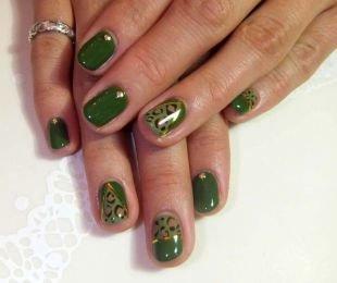 Рисунки фольгой на ногтях, глянцевый зеленый маникюр со стразами на коротких ногтях